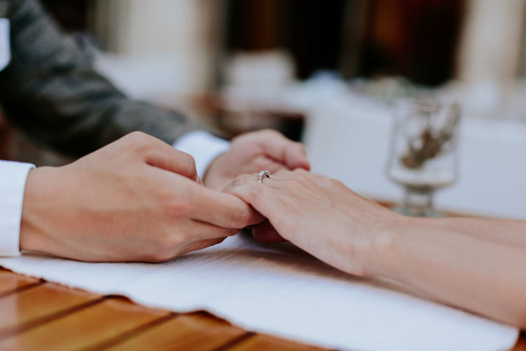 Cropped Image Of Couple Holding Hands At Table