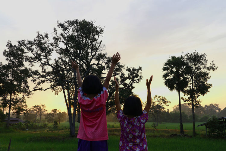 Beauty In Nature Bonding Casual Clothing Childhood Day Field Foggy Forest Gain Fresh Sun Girl Girls Growth Leisure Activity Lifestyles Love Nature Outdoors People Raise Hand Rear View Sky Standing To Rise Togetherness Tree
