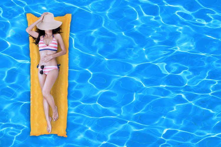 High Angle View Of Woman On Inflatable Raft In Swimming Pool