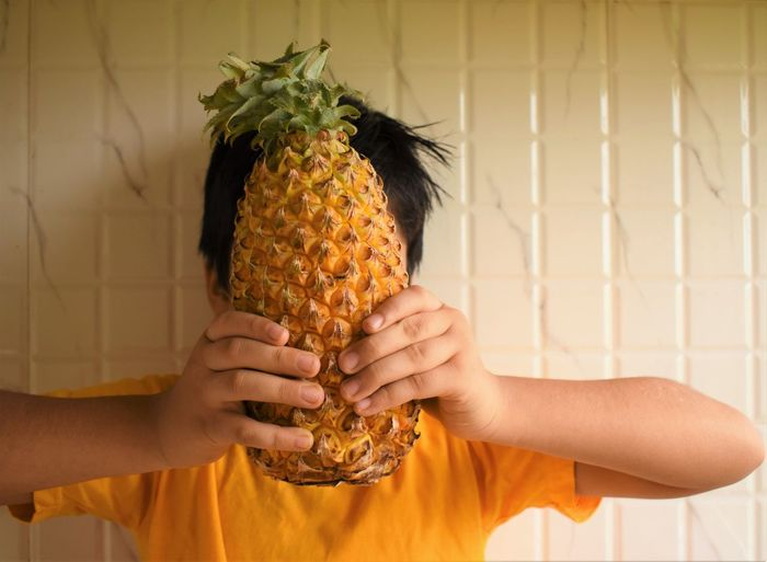 Midsection of boy holding pineapple
