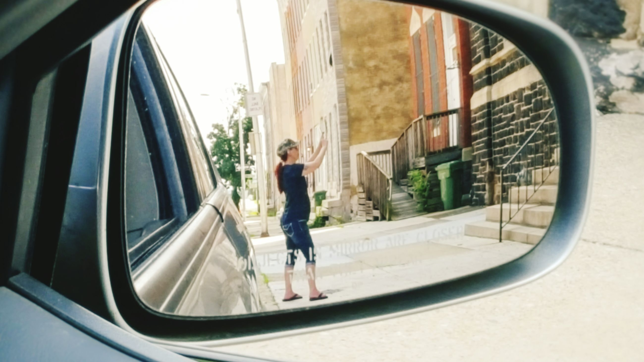 transportation, reflection, side-view mirror, mirror, street, full length, leisure activity, lifestyles, casual clothing, built structure, mode of transport, architecture, building exterior, city life, young adult, day, focus on foreground
