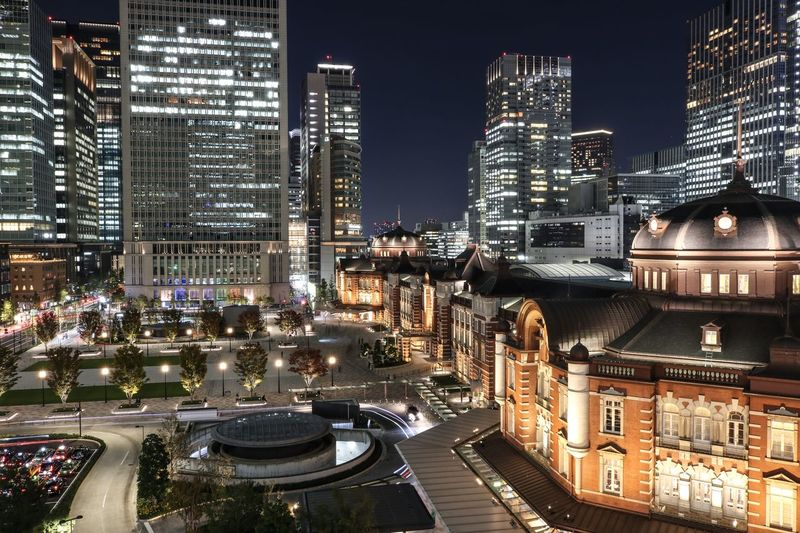 High angle view of illuminated street amidst buildings in city at night