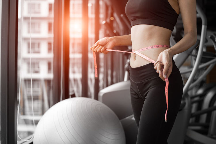 Midsection of woman measuring waist in gym