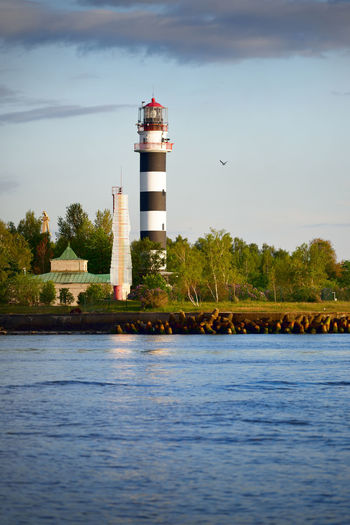 Lighthouse by lake and building against sky