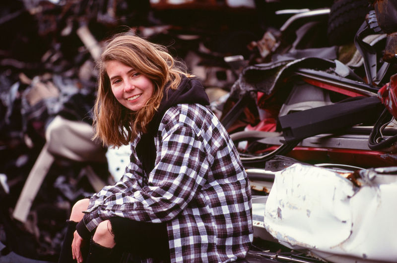 Young woman in an auto salvage yard