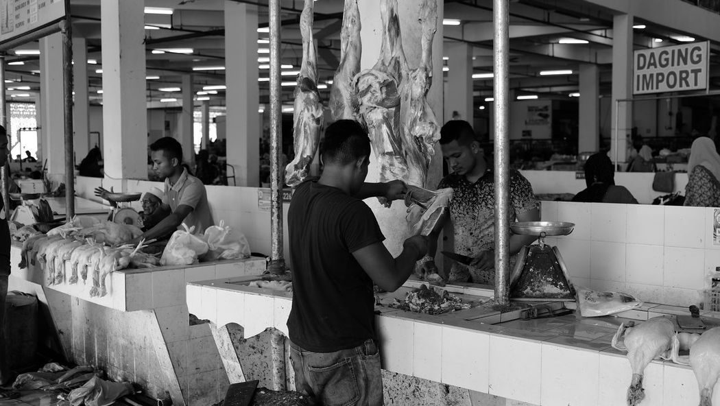 an butcher cutting meat Asian Culture Butcher Cutting Market Activity Casual Clothing Childhood Day Food Indoors  Market Stall Marketplace Meat Pealed Real People Selling Selling On The Street Sitting Standing Wet Market