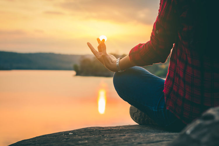 Low section of woman meditating on lakeshore during sunset