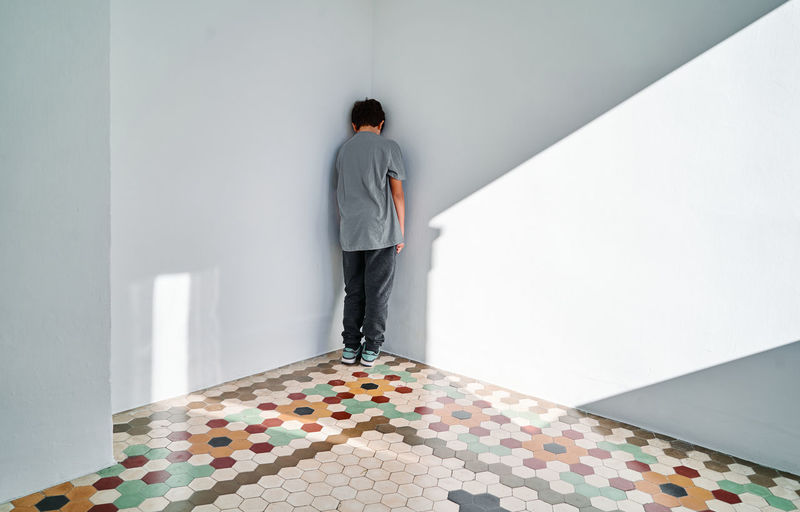 Rear view of man standing against wall at home