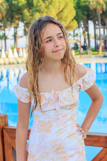 Cute girl looking away while standing by swimming pool