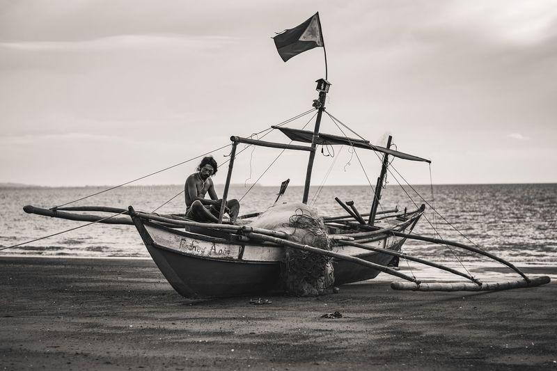 Lone boat in sea against sky