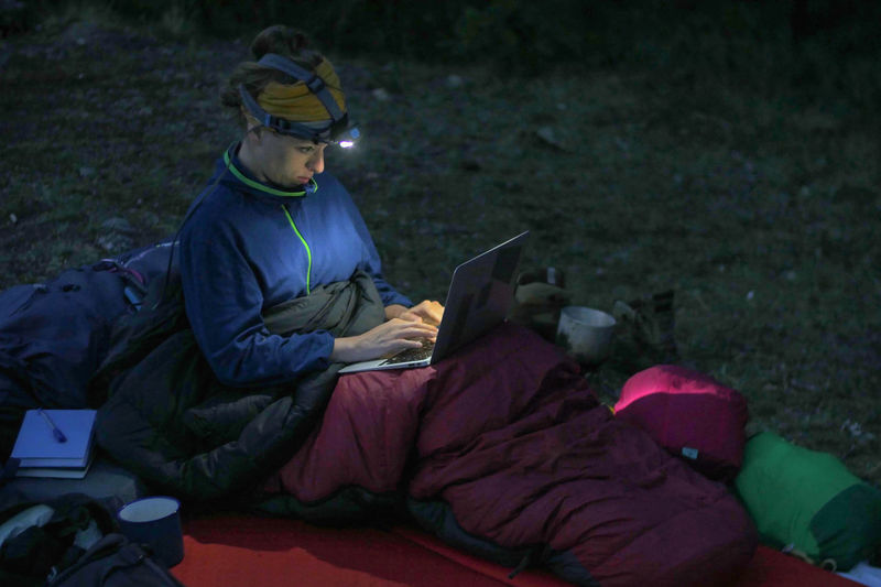 caucasian female hiker working on her laptop at night during wild camping, portable technology concept Backpacking Camping Dark Females Freedom Headlamp Hiking Nature Reading Travel Trekking Working Adventure Battery Clothing Communication Computer Concentration Connection Digital Tablet Evening Full Length Hobby Internet Journal Laptop Leisure Activity Men One Person Outdoors People Portable Information Device Real People Side View Sitting Technology Three Quarter Length Using Laptop Wireless Technology Women