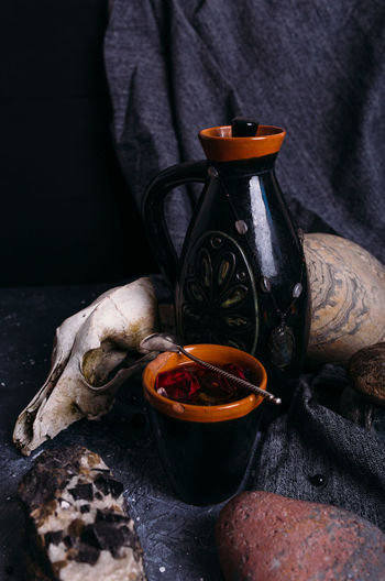 Old dog skull, jug and stones on witch table. enchanted drink with flower petals