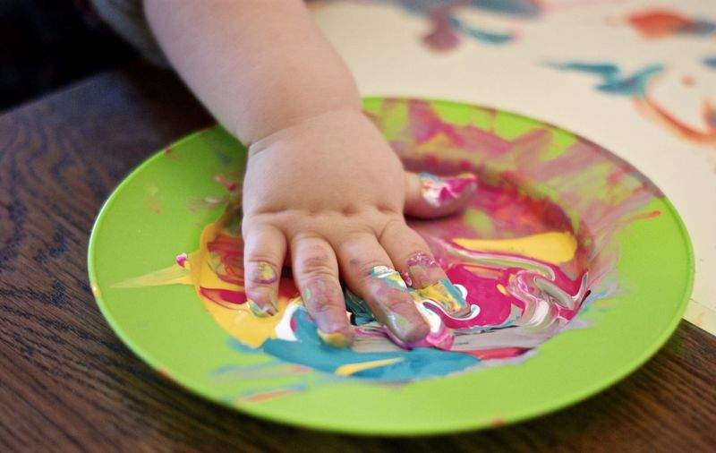 Cropped image of hand on colorful watercolor paints in plate