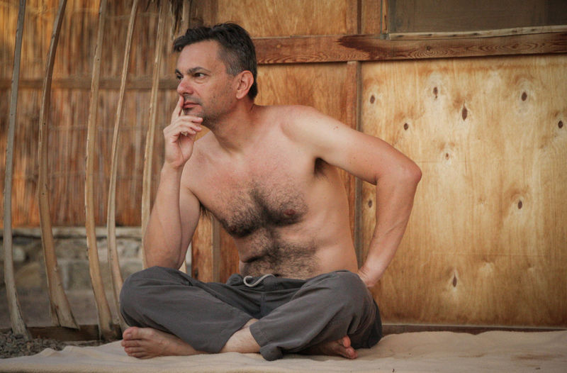 Shirtless man sitting against wooden wall