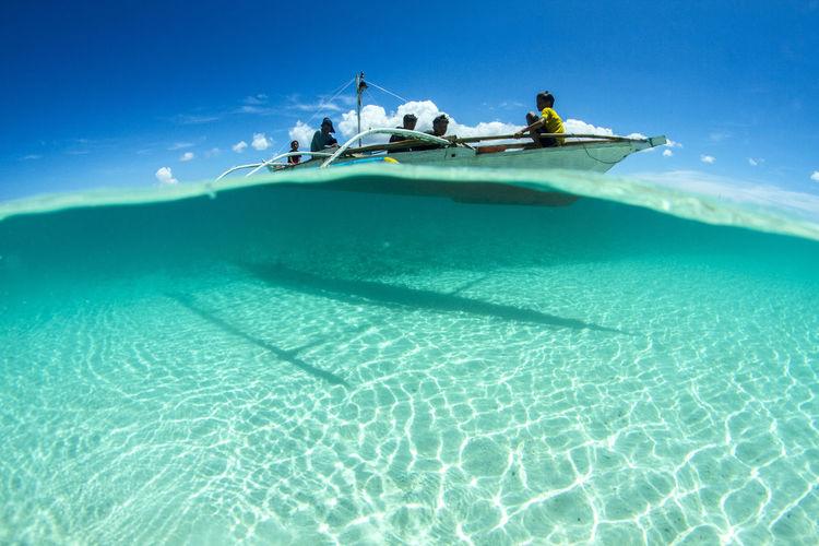 People swimming in pool by sea against blue sky