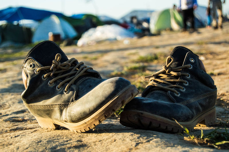 Close-up of shoes on field at refugee camp