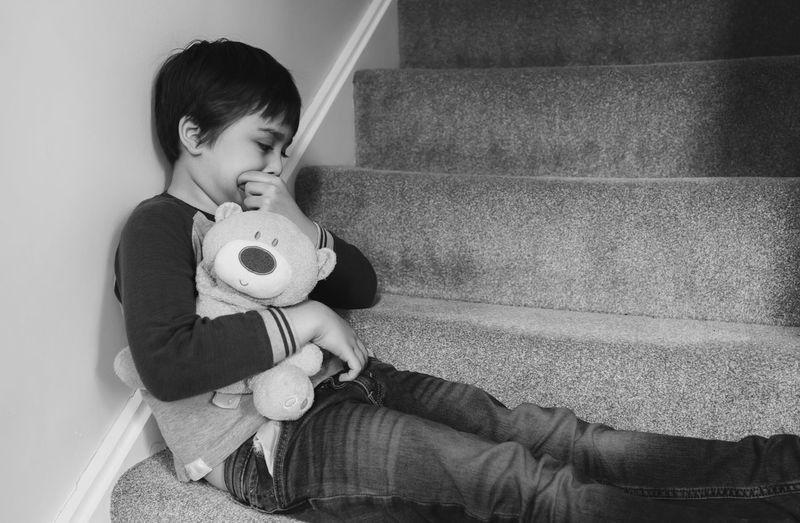 Boy holding teddy bear while sitting on steps