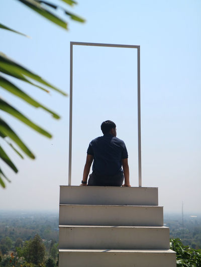 Rear view of man sitting against clear sky