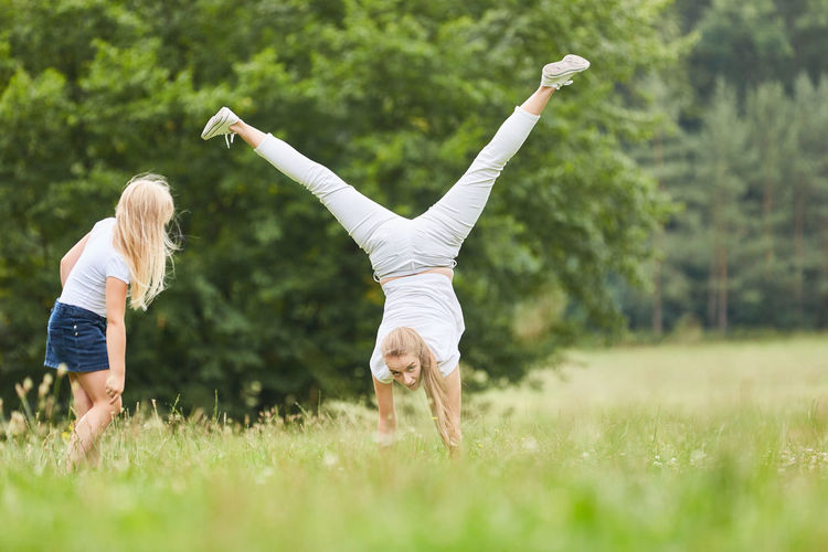 Mother Teaching Handstand To Daughter On Field
