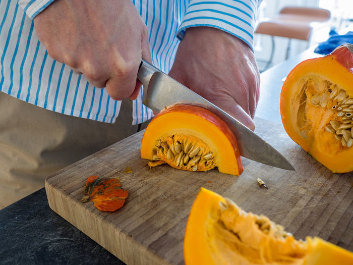 Midsection Of Man Cutting Pumpkin On Board