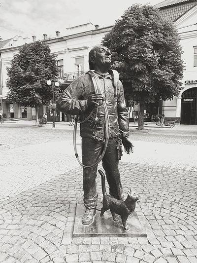 Man on footpath by street in city