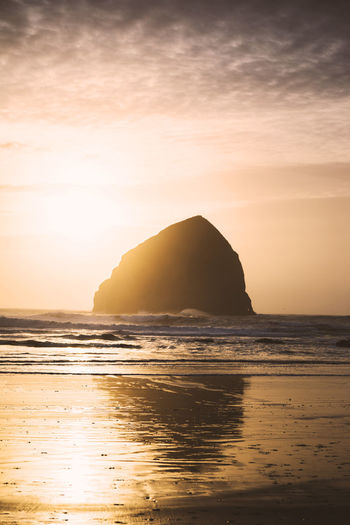 Bright setting sun over Haystack Rock at Cape Kiwanda Beach in Pacific City, Oregon, USA. Cape Kiwanda Pacific City Beach Beauty In Nature Day Horizon Over Water Idyllic Nature No People Outdoors Pacific City Oregon Reflection Rock - Object Scenics Sea Sky Sun Sunset Tranquil Scene Tranquility Water Waterfront