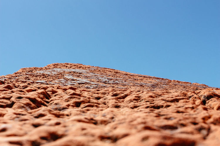 Low angle view of stone wall against clear blue sky