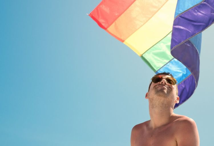 Low Angle View Of Shirtless Young Man With Rainbow Flag Against Clear Blue Sky