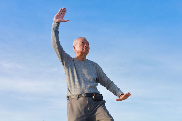 Low angle view of man with arms raised against sky