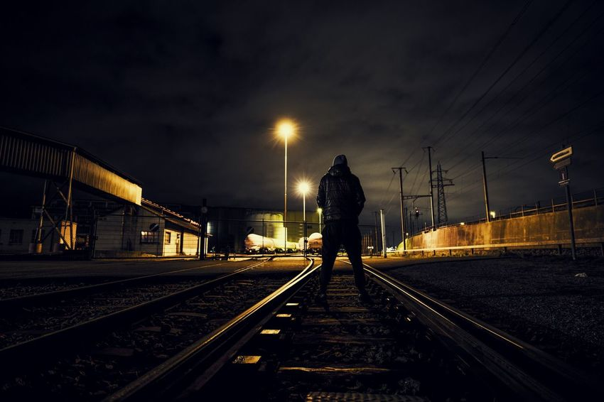 Dark Industrial Industry Low Angle View Electricity  Illuminated Industrial Area Men Night One Person People Rail Transportation Railroad Track Real People Streetphotography The Way Forward Transportation Urban