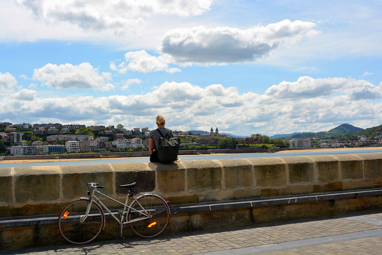 Bicycle by railing in city against sky