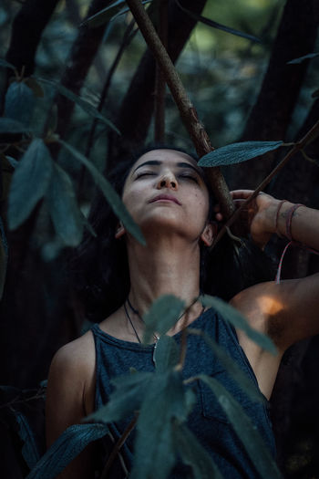 Portrait of woman looking up in forest