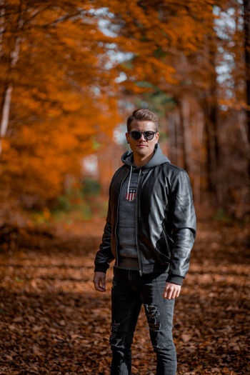 Portrait of young man wearing sunglasses standing outdoors during autumn