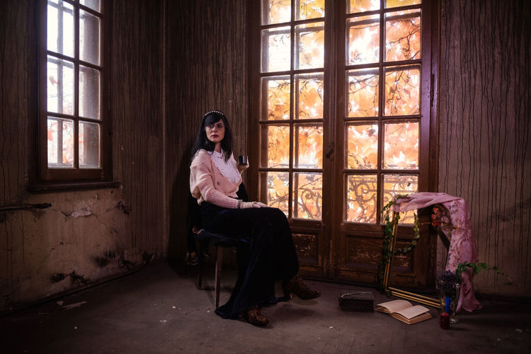 Portrait of man sitting on chair in abandoned house