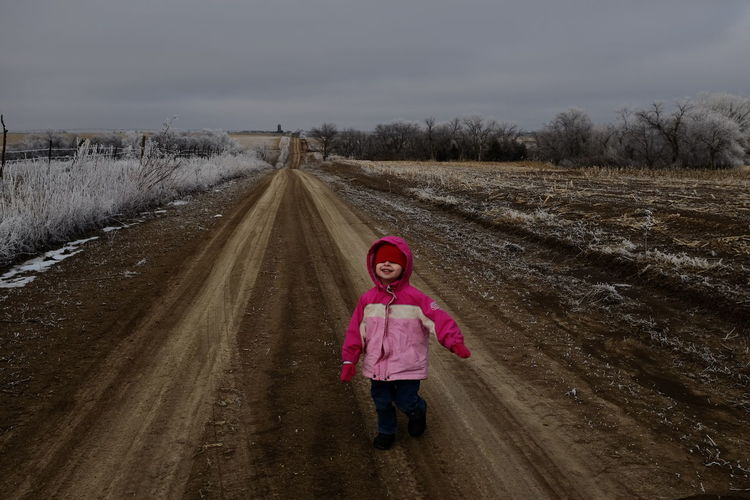 Girl wearing warm clothing on dirt road against sky