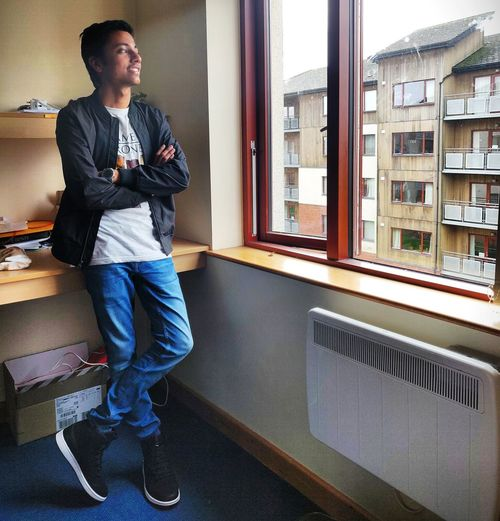 Young man looking away while standing against window