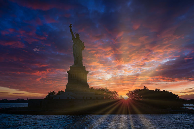 Statue of liberty against cloudy sky during sunset