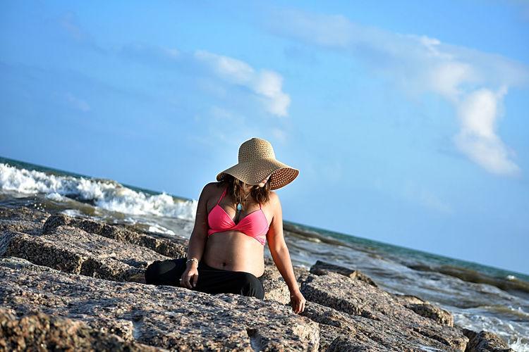 Mid Adult Woman Sitting On Rocks At Beach Against Sky