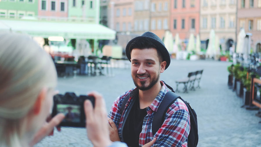 Portrait of smiling young man using mobile phone in city