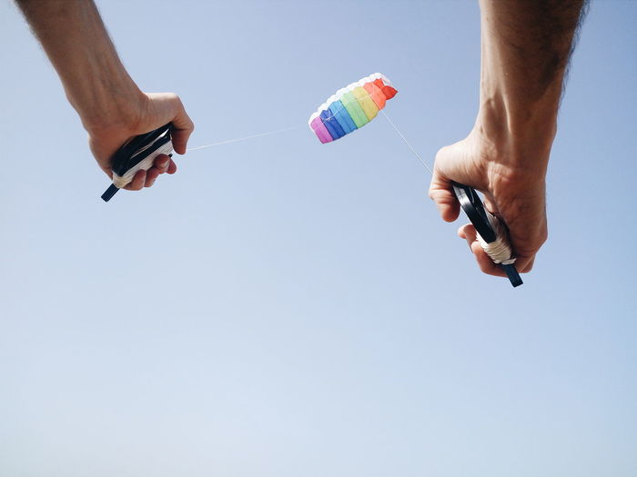 Low Angle View Of Person Holding Handles Of Parachute