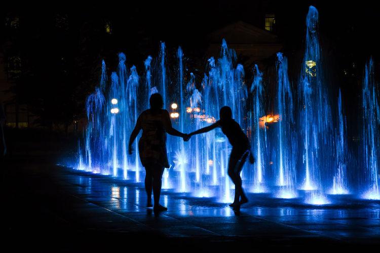 Silhouette men standing against illuminated lights
