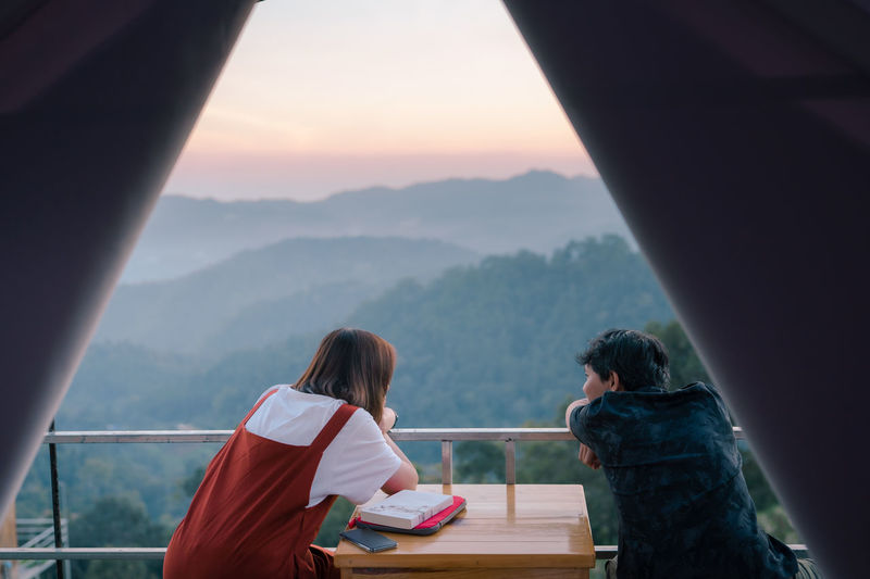 Asian couple relax with travel in honeymoon trip with mountain background