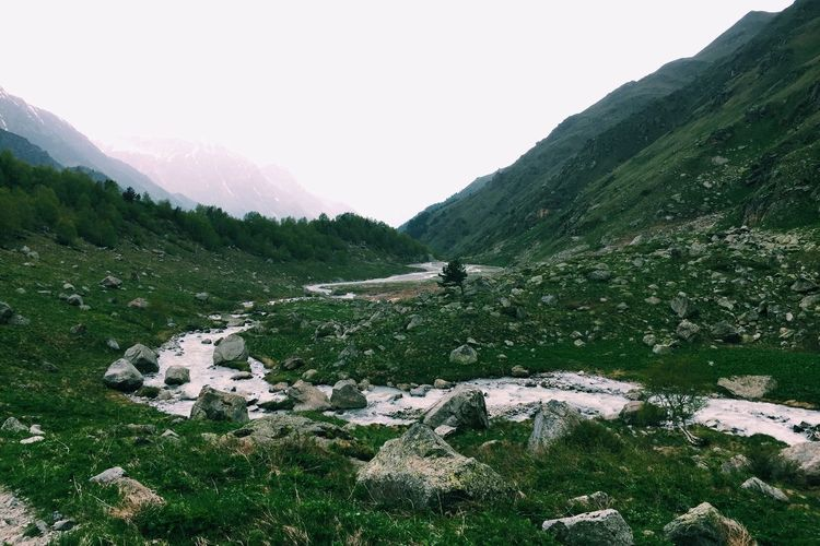 Scenic view of stream in valley against sky