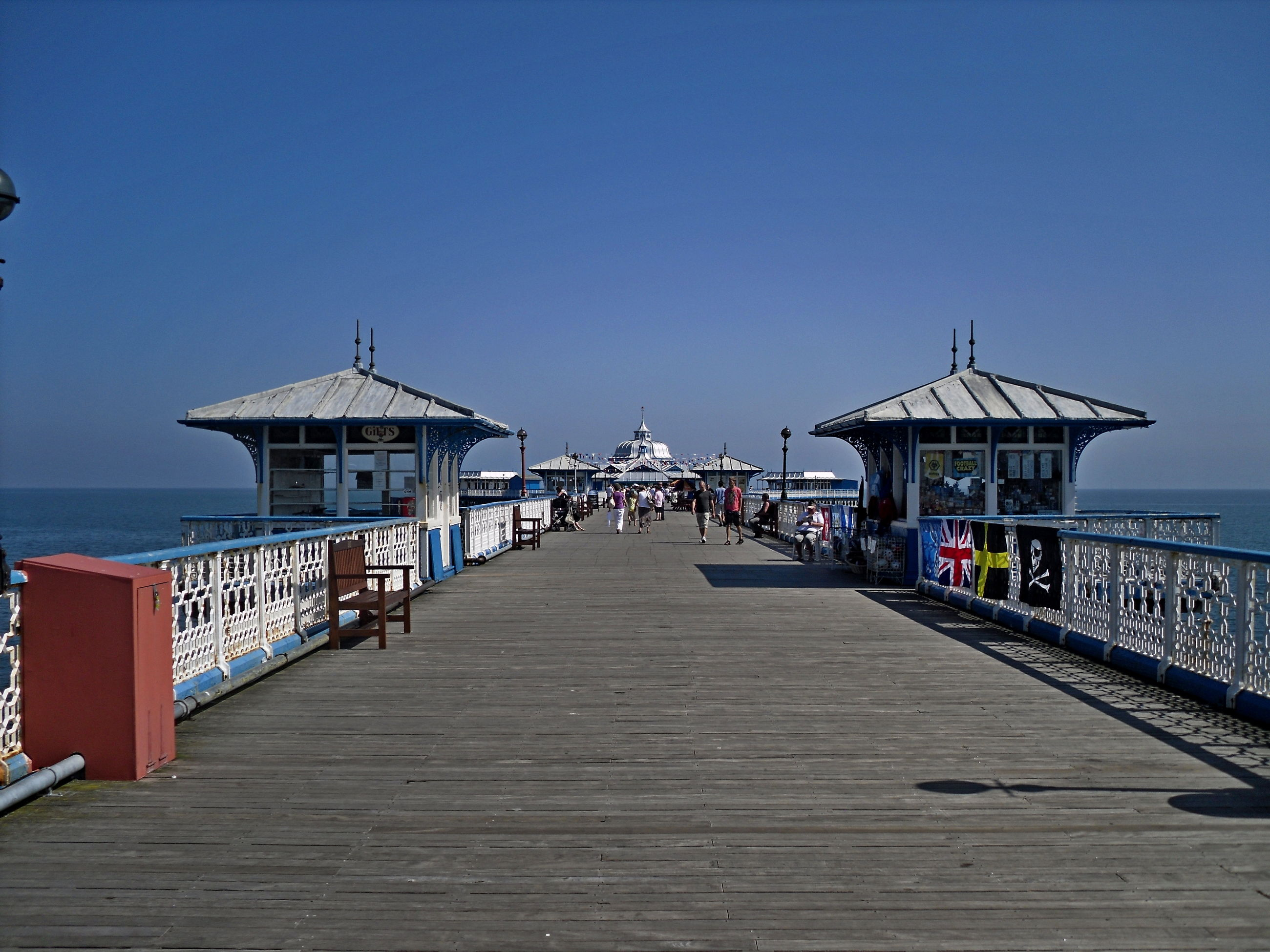 water, pier, sea, clear sky, beach, outdoors, nature, day, horizon over water, jetty, tranquil scene, blue, sky, tranquility, real people, scenics, beauty in nature, large group of people, wood paneling, people
