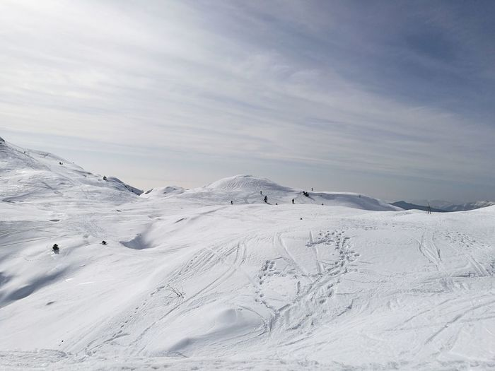 Scenic view of snow covered mountains against light blue sky