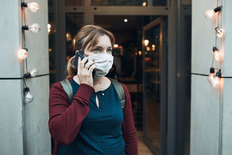 Young woman talking on phone standing in a front of restaurant downtown wearing the face mask