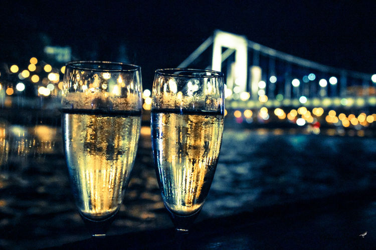 Close-Up Of Champagne Flutes Against Illuminated City At Night
