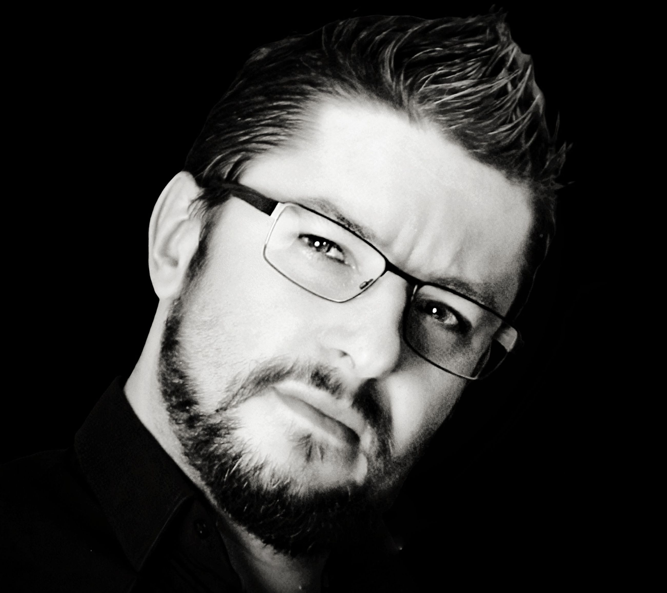 portrait, one person, black and white, beard, headshot, eyeglasses, facial hair, black background, glasses, adult, monochrome photography, men, studio shot, monochrome, indoors, black, human hair, looking at camera, close-up, human face, moustache, vision care, eyewear, serious, young adult, front view, portrait photography, hairstyle, contemplation, looking, lifestyles, white, stubble, person, copy space