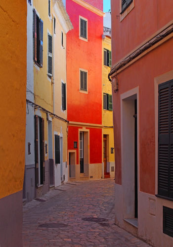 brightly painted traditional houses on a cobbled quiet curved empty street in ciutadella menorca with wooden shutters and a blue su Ciutadella Street Menorca Multi Colored Cobblestone Town Alley Day Architecture Building Exterior Window City Residential District No People House Door Entrance Tourism Destination