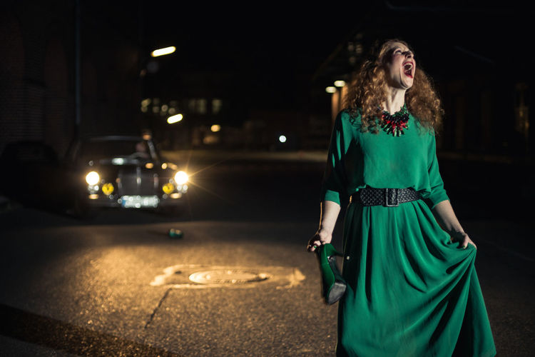 Young Woman Screaming Against Vintage Car On Road During Night